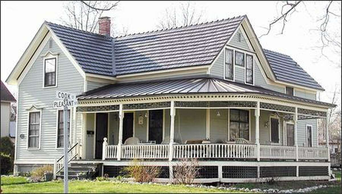 Installing a metal roof, such as this simulated cedar shake aluminum one on the main house and the standing seam roofing on the porch, can earn homeowners a tax credit of $500. (CLASSIC PRODUCTS)