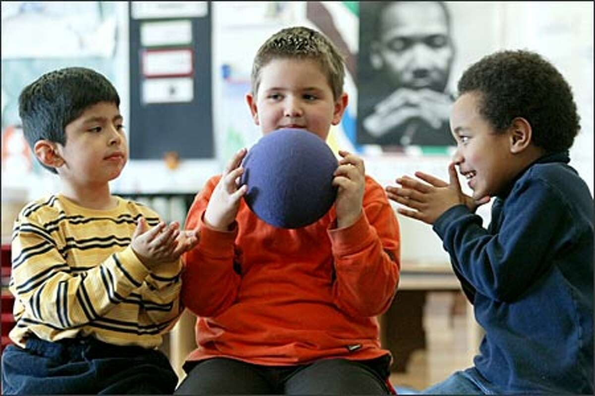 Kindergarters Armando Antmio, left, Erik Hansen, center, and Eleanor Waganisau play a game of