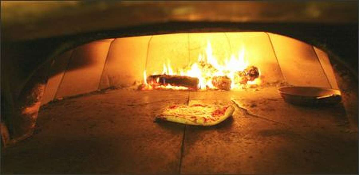 One of five thin crust pizzas on the menu bakes in the wood-burning oven at The Hi-Life in Ballard. Also from the oven come wood-roasted chicken platters for two or more.
