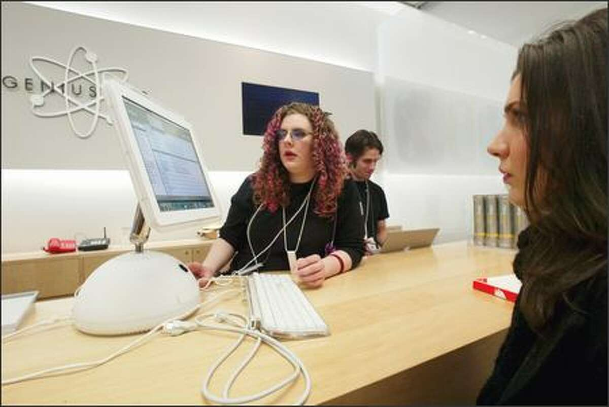 Tech Julie Atwood, left, helps Erin Kolmodin yesterday at Apple's Genius Bar in University Village. Marlon Schaeffer, center, also is a Genius tech.