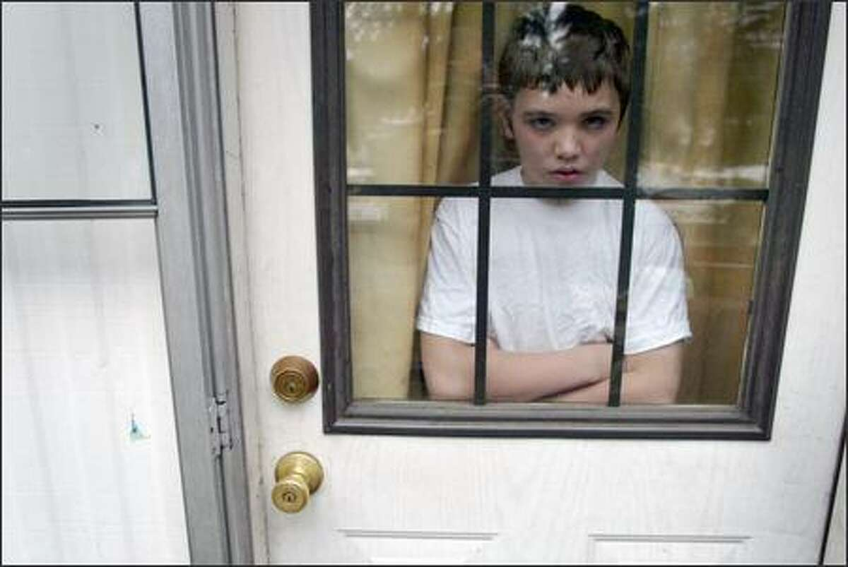 Curtis, 13, peeks from the front door of his SeaTac home, where he spent five weeks on house arrest after being charged last fall with burglary. While the P-I rarely identifies minor offenders in juvenile justice stories, Curtis and his guardian agreed to be interviewed and photographed.