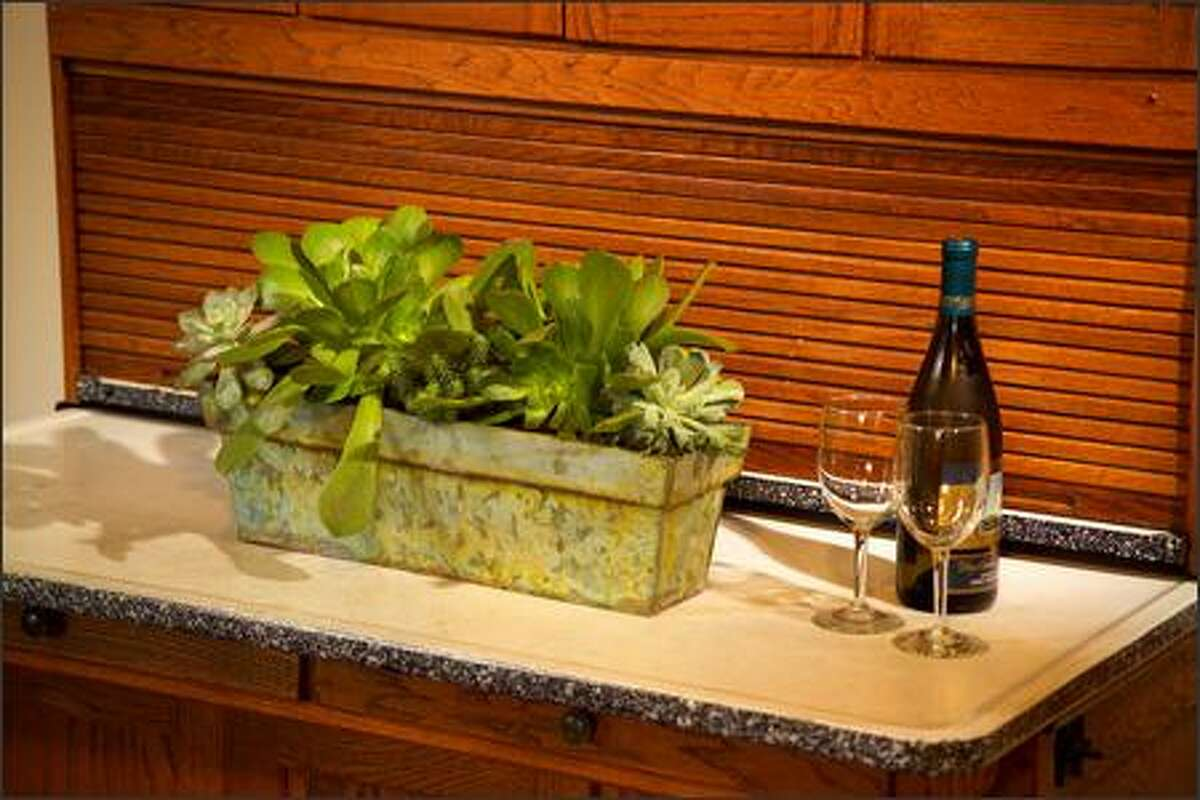 Planted with sedums and succulents, a zinc box brings the garden to the kitchen. This one is filled with interesting Echeveria and Aeonium cultivars.