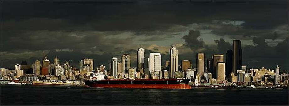 The Ever Young sits anchored in Elliott Bay as dark storm clouds surround the Seattle skyline. Photo: Gilbert W. Arias, Seattle Post-Intelligencer / Seattle Post-Intelligencer