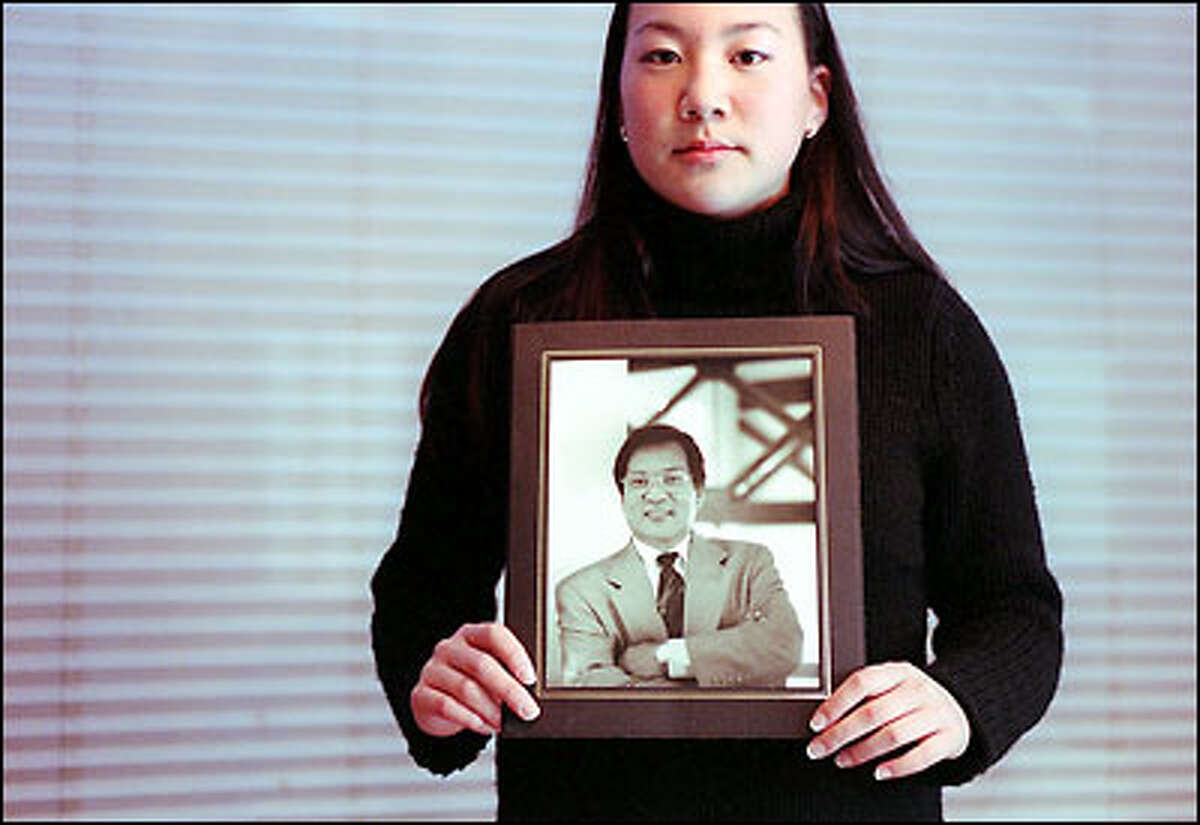 Sharon Kim holds a photograph of her father, Yongsu, who was slain three months ago outside his service station and convenience store. Sharon says she considered her father a best friend.
