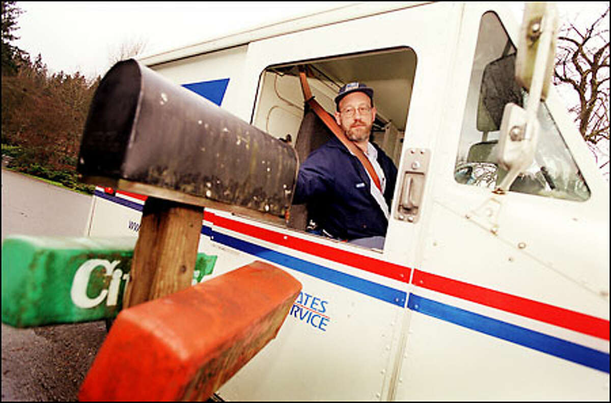 Postal carrier Brooks Bennett delivers mail in a neighborhood off Riverside Drive West in Bothell.