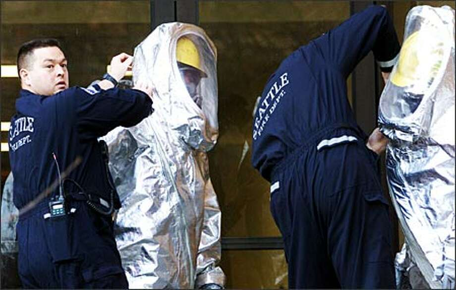 Firefighters get into their hazardous-material suits before entering the Aerospace and Engineering Research Building on the University of Washington campus Tuesday to check out a chemical spill on the third floor. Photo: Loren Callahan, Seattle Post-Intelligencer / Seattle Post-Intelligencer