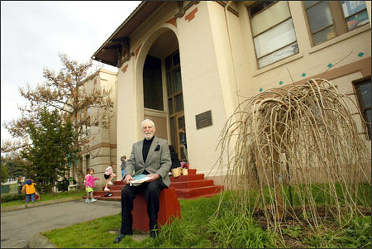 Phil Flash, head of the Mercer Island Historical Society, sits by the Boys & Girls Club, in the old East Seattle School. Flash is trying to save the building from destruction.