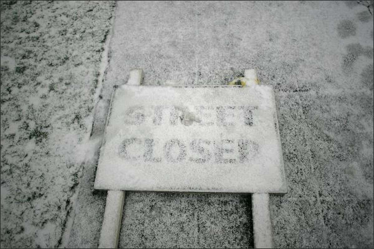 Snow falls on a road sign in Queen Anne.