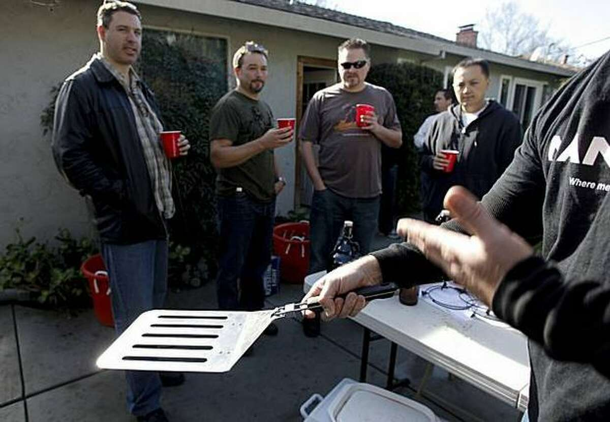 Man Cave salesman John Schaffran displays the $25, four-burger spatula that was one among many Man Cave barbecue products, which were available at this San Jose backyard sales party for men, a male version of the Tupperware party.