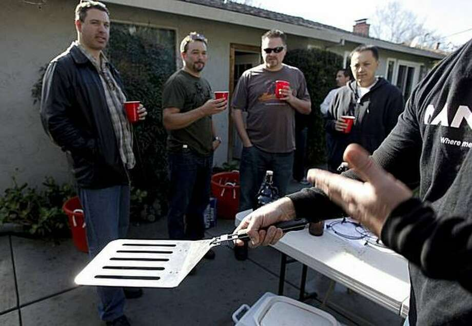 Man Cave salesman John Schaffran displays the $25, four-burger spatula that was one among many Man Cave barbecue products, which were available at this San Jose backyard sales party for men, a male version of the Tupperware party. Photo: San Francisco Chronicle / San Francisco Chronicle