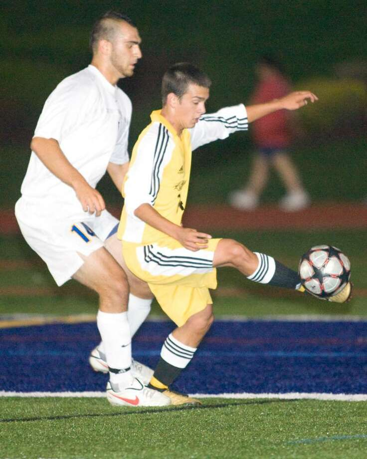 Dean Basak Smith of Joel Barlow gets a foot on the ball despite the tight marking of Brookfield's Chris Ackell Thursday night at Brookfield High. Photo: Barry Horn / The News-Times
