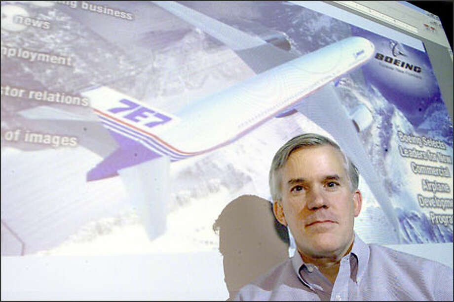 Mike Bair, senior vice president for Boeing's Commercial Aviation Services, stands in front of a computer-generated image of the proposed 7E7. Photo: Loren Callahan, Seattle Post-Intelligencer / Seattle Post-Intelligencer