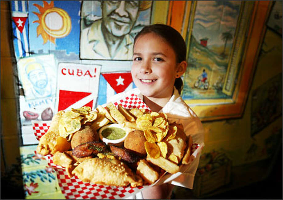 Ali D'Arco- Rinaldo, 10, daughter of bistro owners Angela Rinaldo and Miriam D'Arco, holds up a Combination Cubana platter of goodies from empanadas and mariquitas to plaintain chips, tostones and yuca root. Photo: Scott Eklund, Seattle Post-Intelligencer / Seattle Post-Intelligencer
