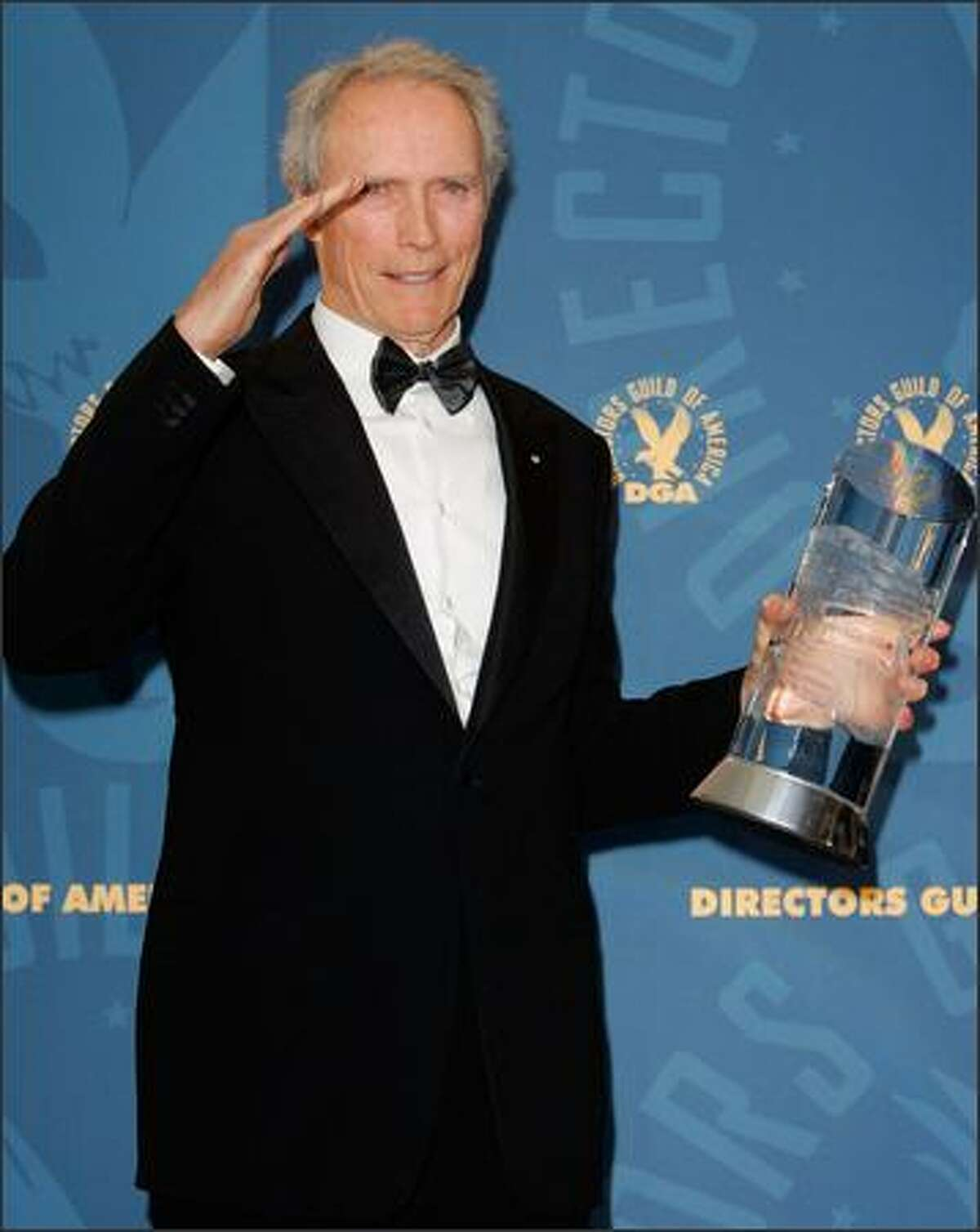 Clint Eastwood salutes backstage as he poses with the Directors Guild of America lifetime achievement award at the 58th Annual Directors Guild Awards in Los Angeles, on Saturday, Jan. 28, 2006. (AP Photo/Mark J. Terrill)