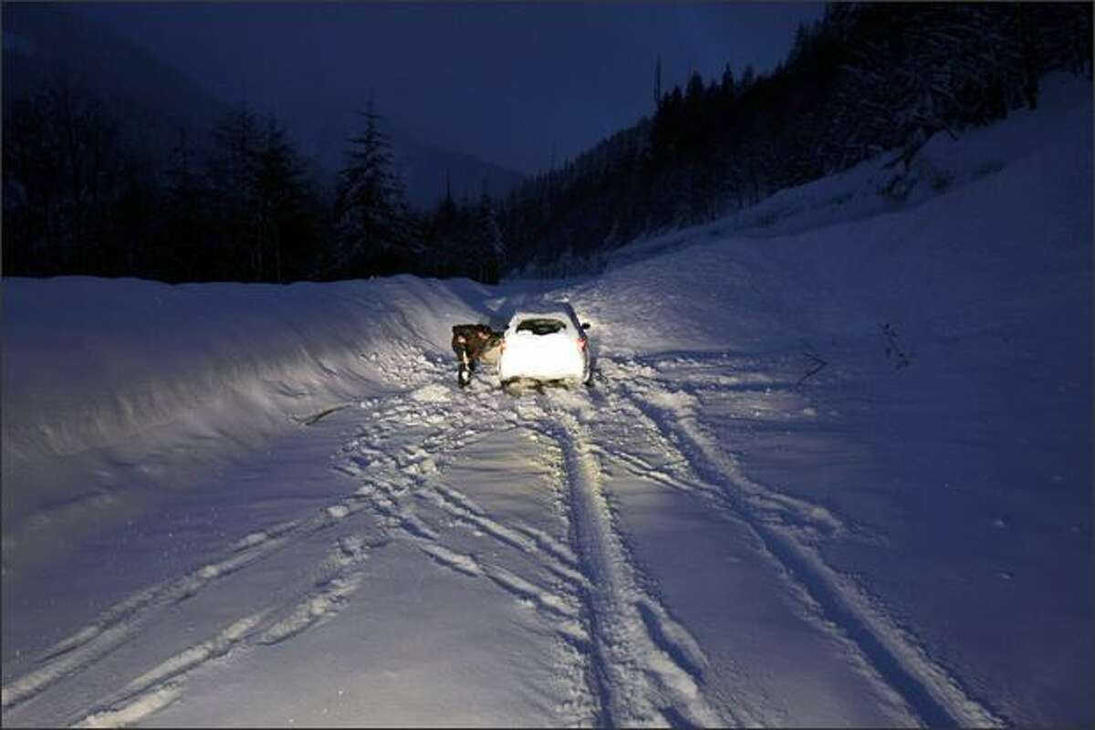 A driver tries to free his car after driving into an approximately 30-foot wide snow slide spanning eastbound I-90 in the Lower Granite Mountain area, which was released by charges set by the DOT to control avalanches at Snoqualmie Pass. The driver was traveling a closed section of the freeway and was sent back the way he came after being freed by DOT workers.