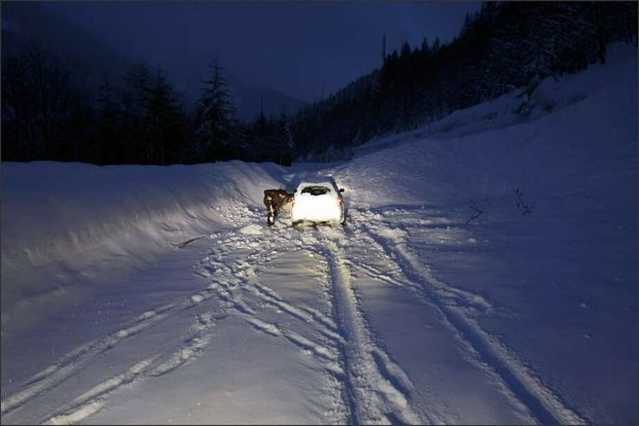 A driver tries to free his car after driving into an approximately 30-foot wide snow slide spanning eastbound I-90 in the Lower Granite Mountain area, which was released by charges set by the DOT to control avalanches at Snoqualmie Pass. The driver was traveling a closed section of the freeway and was sent back the way he came after being freed by DOT workers. Photo: Andy Rogers, Seattle Post-Intelligencer / Seattle Post-Intelligencer