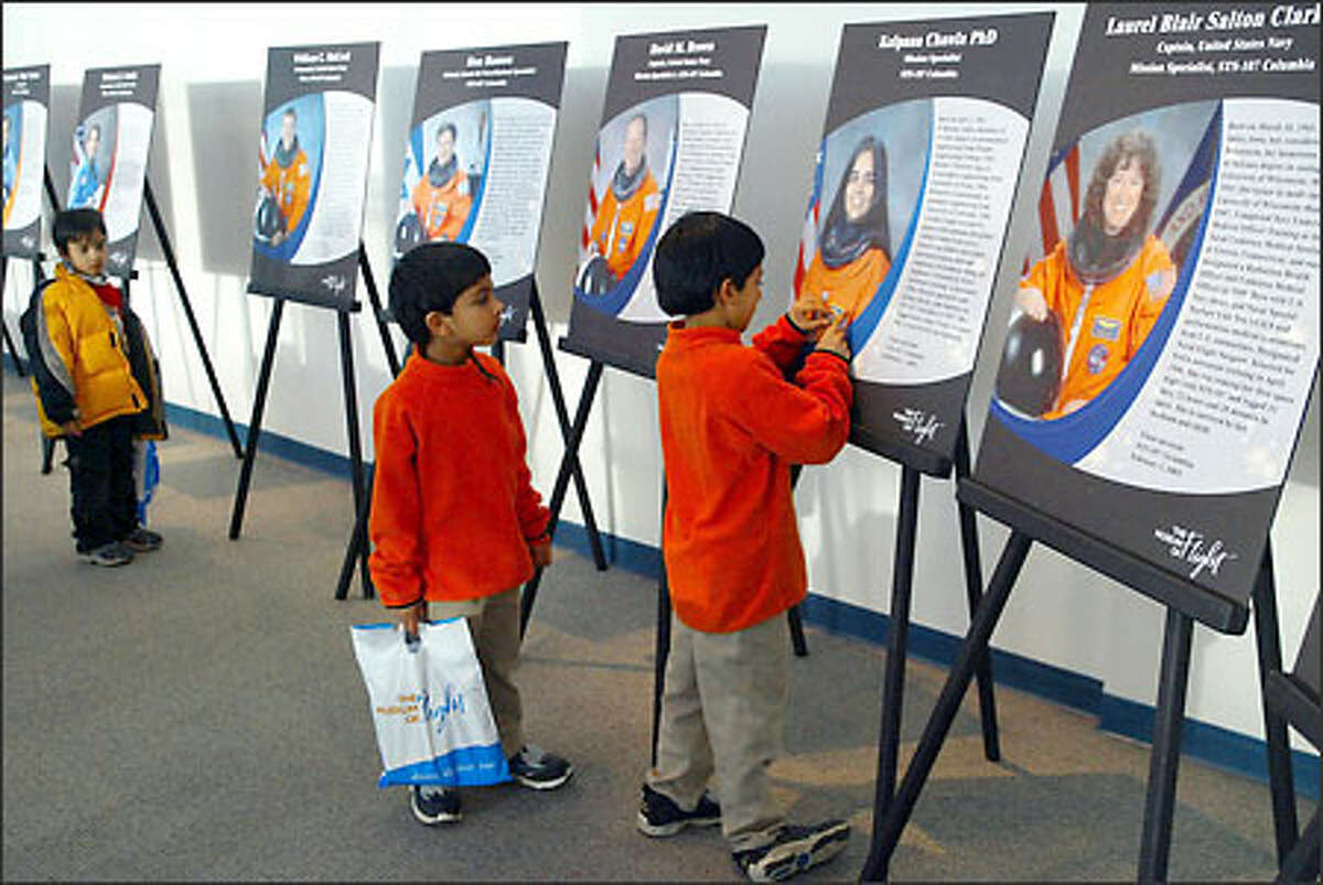 Avi Parikh, 6, of Kirkland and his brother, Devon, 4, look at a photo of Kalpana Chawla, who died on the Columbia space shuttle, at the Museum of Flight yesterday. Seven astronauts died in the Columbia tragedy during re-entry into the Earth's atmosphere last February.