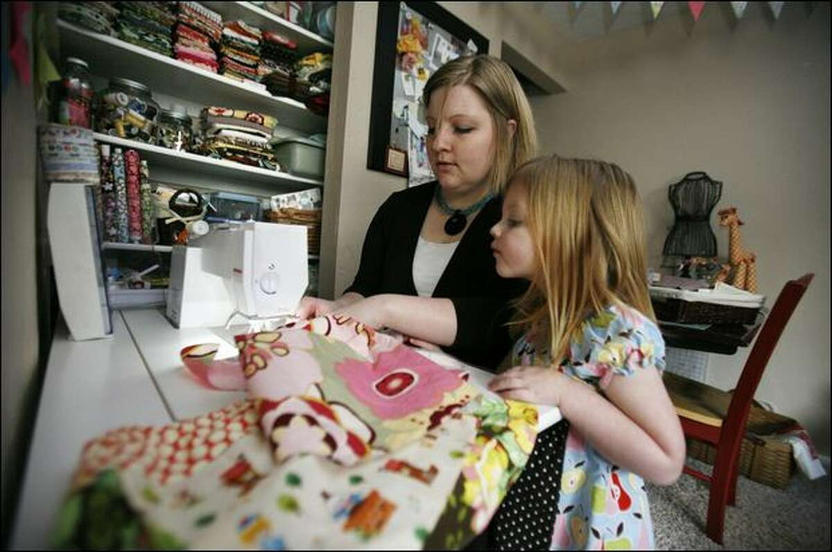 Sara Collett makes children's clothing to sell on the Internet. She is working on a dress in her Redmond home on Wednesday while her 3-year-old daughter Macy watches.
