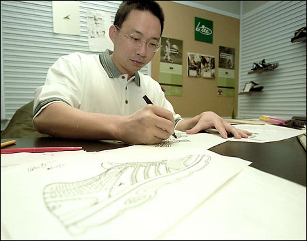 Kevin Xiao, director of design and development for Bite Footwear in Preston, works on a golf sandal. Owners of Bite products swear by their comfort.