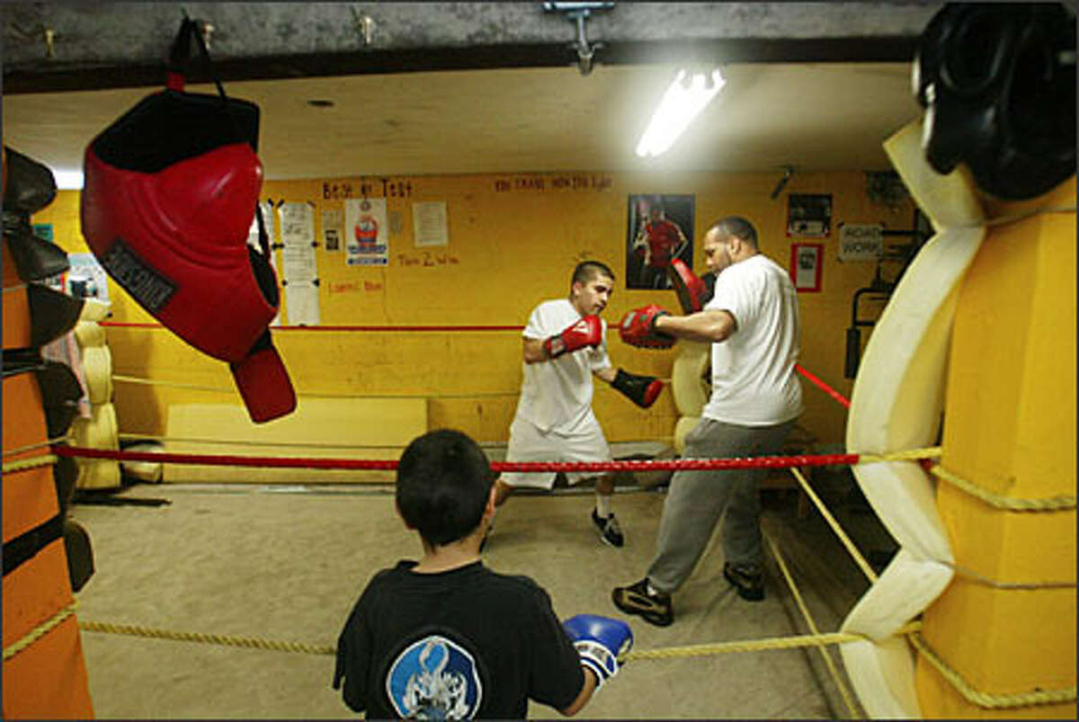 Rafael Garcia, 7, watches Randy Gomez, left, work out with trainer Ray Murray. The focus and direction Gomez has gained in the gym has helped him with other aspects of his life, such as high school and his part-time job, too.