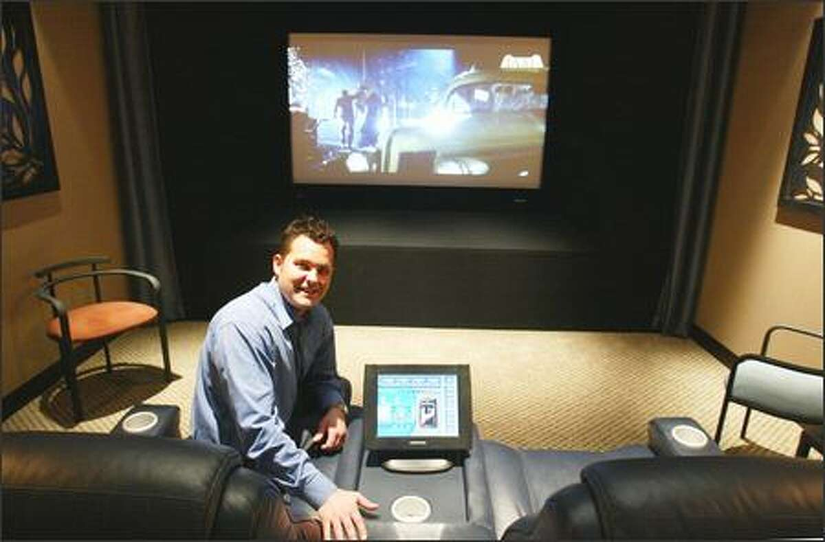 Lee Travis, chief executive of Home Technologies Inc., shows off a demonstration theater at the company office in Bellevue. The firm installs sound and movie systems and home computer networks. It grew last year via several acquisitions, but Travis wants a network of franchises.
