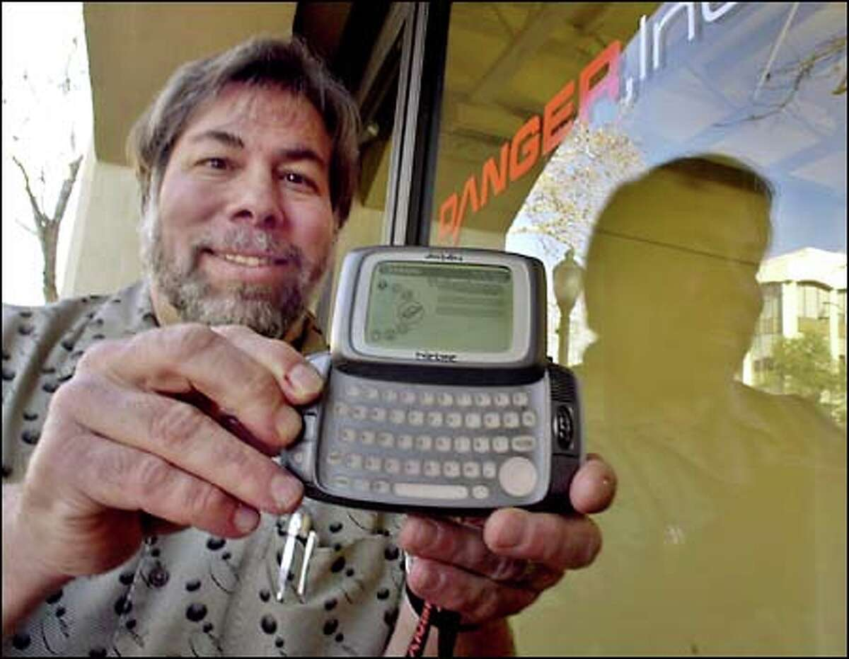 Apple Computer co-founder Steve Wozniak, a member of the board of directors of Danger Inc., displays Danger's multifunction hand-held device.