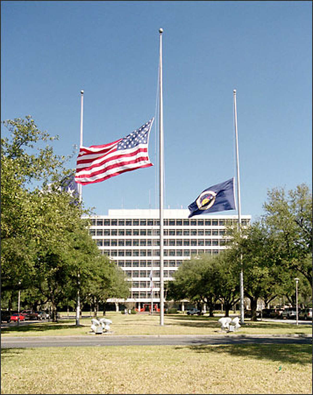 Flags fly at half mast in front of the administration building at the Johnson Space Center in honor of the crew of the Columbia space shuttle.
