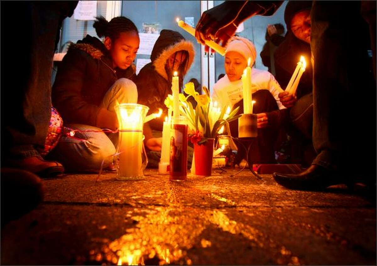 Family members place candles in front of the Philadelphia Cheese Steak restaurant during a memorial Friday for owner Degene Barecha, who was slain Wednesday.
