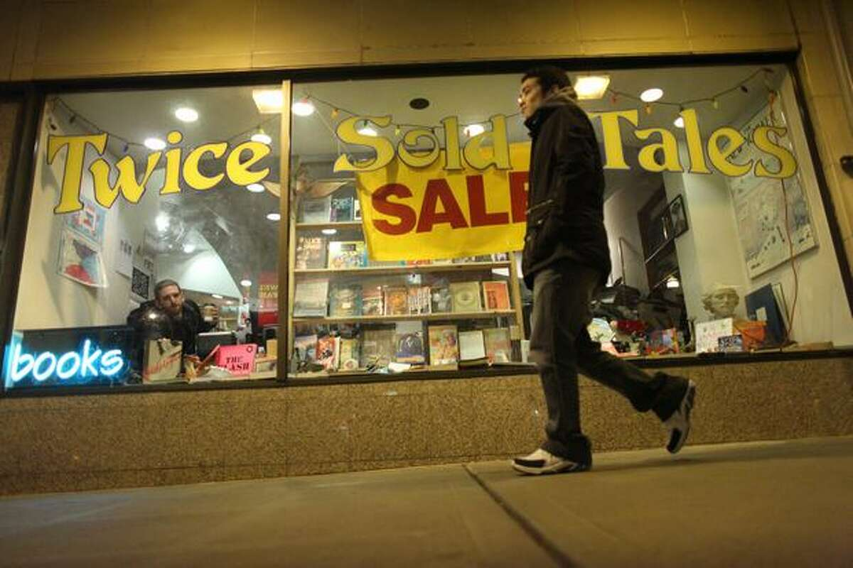 A pedestrian walks past Twice Sold Tales on University Avenue on Wednesday. The U District bookstore will close and become an online-only operation, while the Capitol Hill store will stay open.
