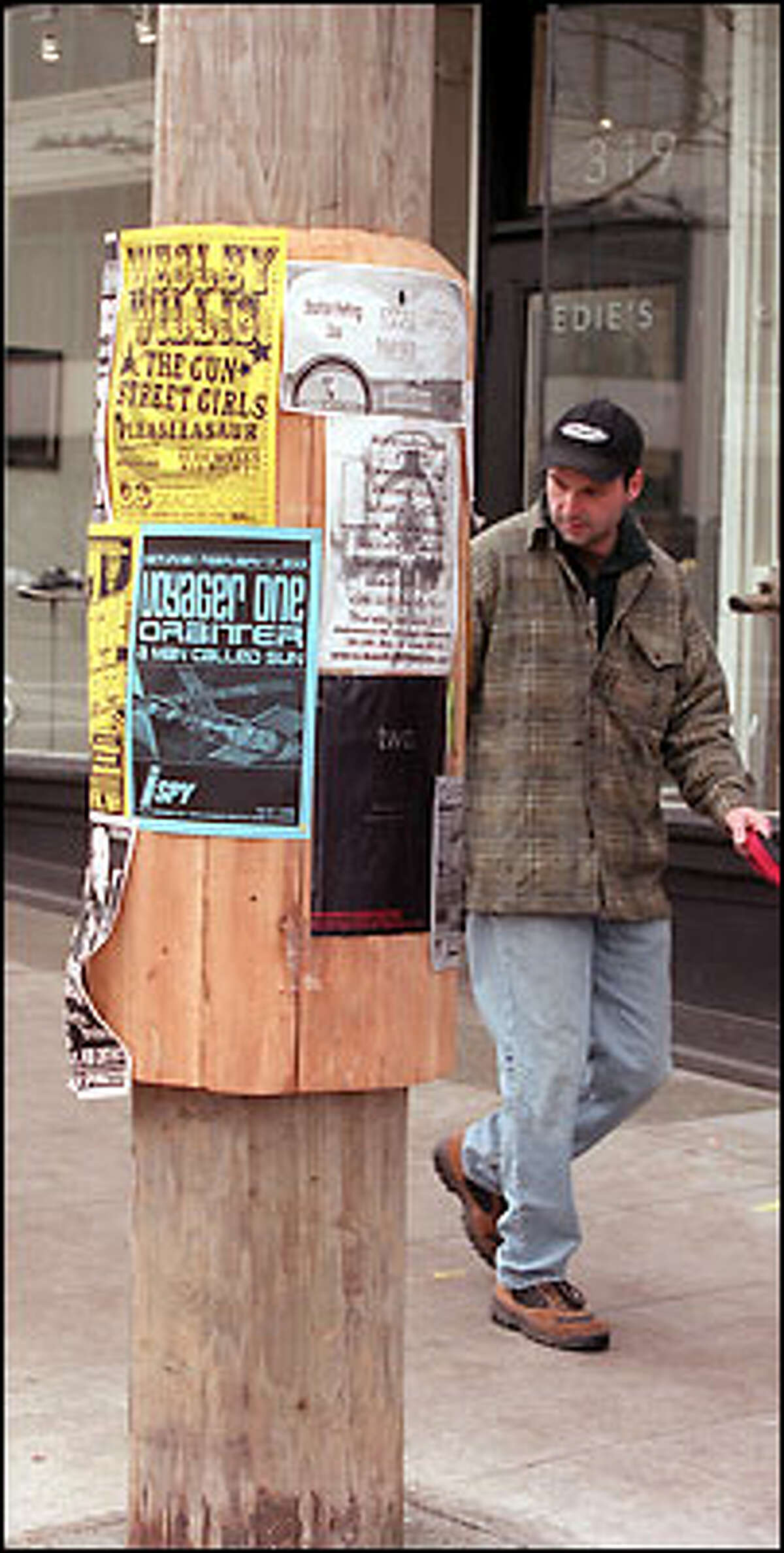 Troy Curley walks past a new kiosk on East Pine in Seattle. The city has been installing public kiosks for about a decade, but questions linger over whether they're actually legal. Now the City Council plans to settle the issue once and for all.