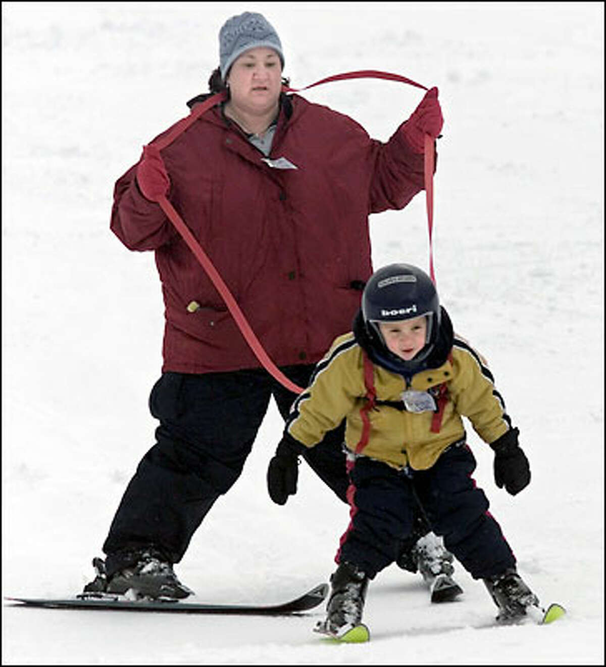 Tyler Thurman learns the ropes of skiing with his mother, Doreen. The 3-year-old would have preferred to snowboard yesterday at Snoqualmie Pass, but his mother advised skis first. Tyler's experience with ice hockey helped him look like a pro.