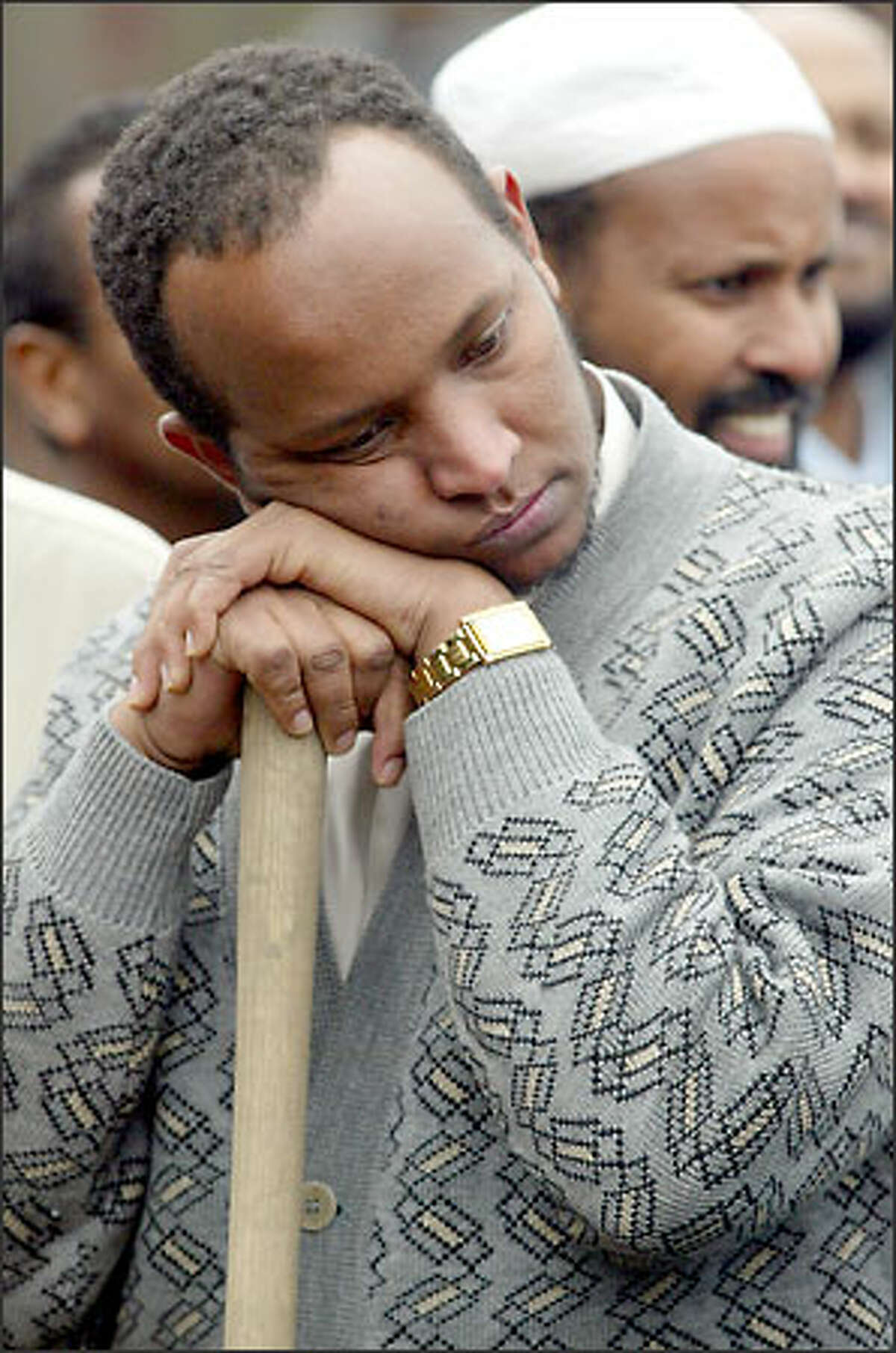 Abdi Ashoor leans on a shovel as he waits to be among the first to place earth on the grave of his slain cousin, Hassan Farah, who was shot to death Saturday while driving his cab.