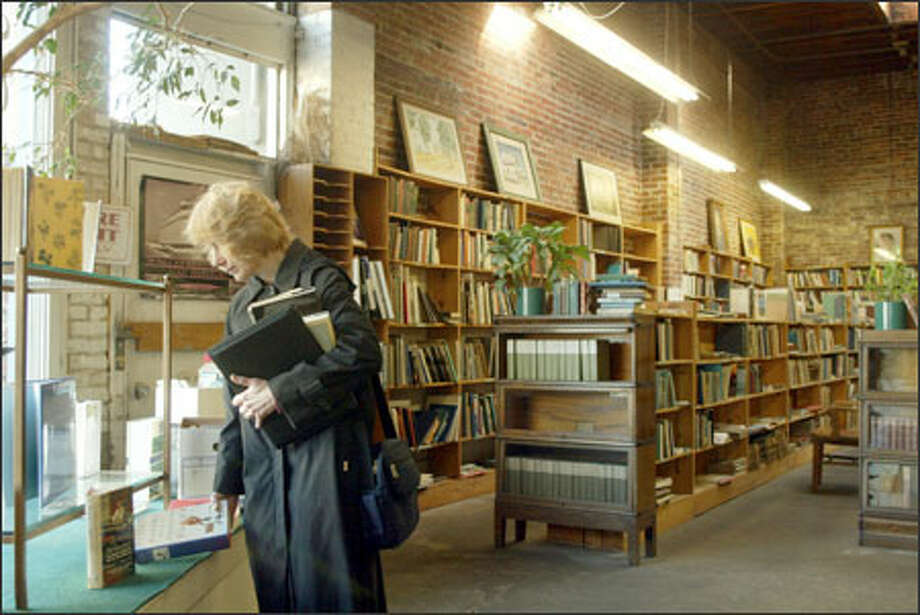 Lyn Playle looks for bargains at Fillipi Book and Record Shop, which is closing soon on Capitol Hill after 70 years as a Seattle business. Owner Brenda Fillipi, 65, says she wants to spend more time with her husband, Ian MacGowan. In 1935, Fillipi's parents, Ted and Kits, started the store on Third Avenue after her mother convinced her father that San Francisco – where they fell in love – had too many bookstores. The store has been at 1351 E. Olive Way since 1952. Fillipi is selling the building. Playle was looking for sale items for a bookstore she's opening in Port Gamble in May. Photo: Phil H. Webber, Seattle Post-Intelligencer / Seattle Post-Intelligencer