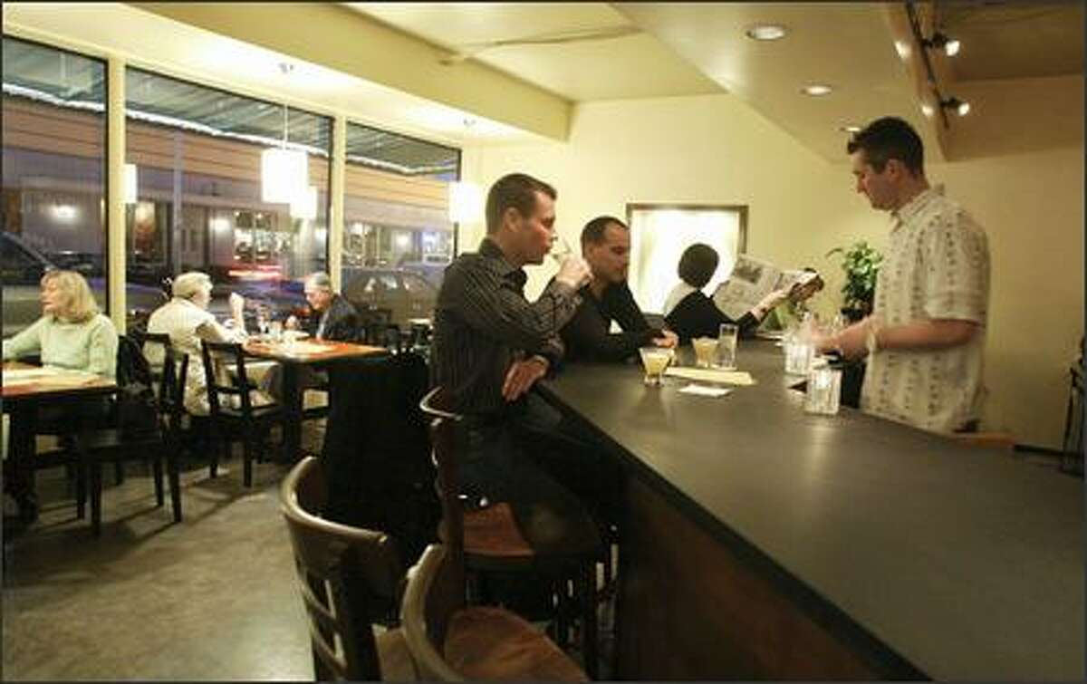 Out-of-town businessmen Ryan Fischry, left, and Darren Taylor are served by bartender Chris Carter at Moxie. The full bar also has about a dozen wines by the glass.