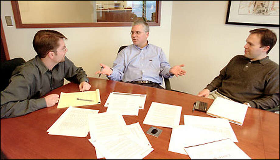Sightward President and CEO Kevin Klustner, center, chats with Michael Smith, left, and Jeffrey Bede of Capital Run during a meeting at Capital Run's office in Two Union Square. Photo: Seattle Post-Intelligencer / Seattle Post-Intelligencer
