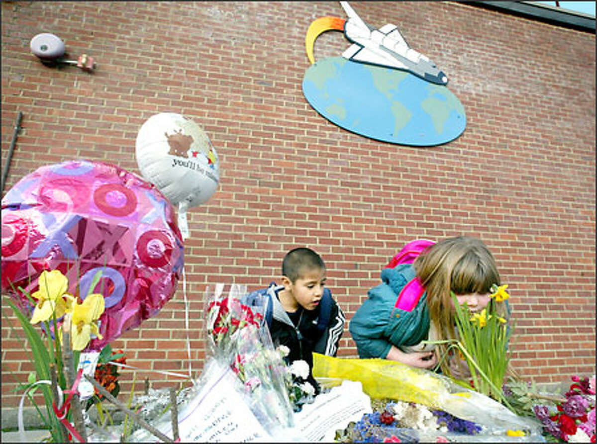 Alexis Embody stops to smell flowers left by children at Dick Scobee Elementary School in Auburn as part of a memorial for the Columbia space shuttle victims. With her is fellow first-grader Edgar Lopez. Pupils also left candles, flags and letters to the crew members.