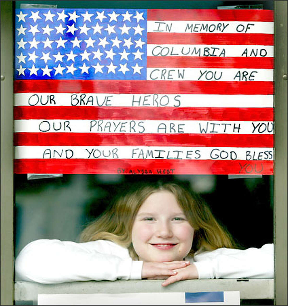 Fourth-grader Alyssa West with the American flag she spent four hours making to honor Columbia's crew. The flag is displayed at a school entrance.