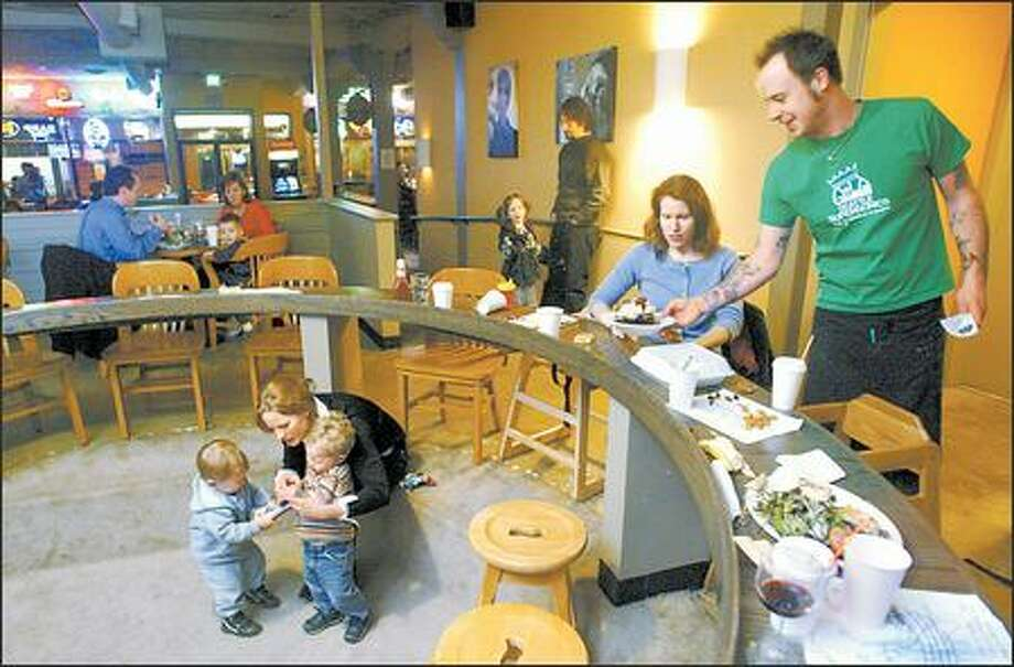 Christina McCracken is served by Josh Baymiller at Montlake Ale House as fellow mom Megan Bartot mediates a toddler tug-of-war between Max Bartot, 1, and Whit McCracken, 1. Photo: Mike Urban, Seattle Post-Intelligencer / Seattle Post-Intelligencer