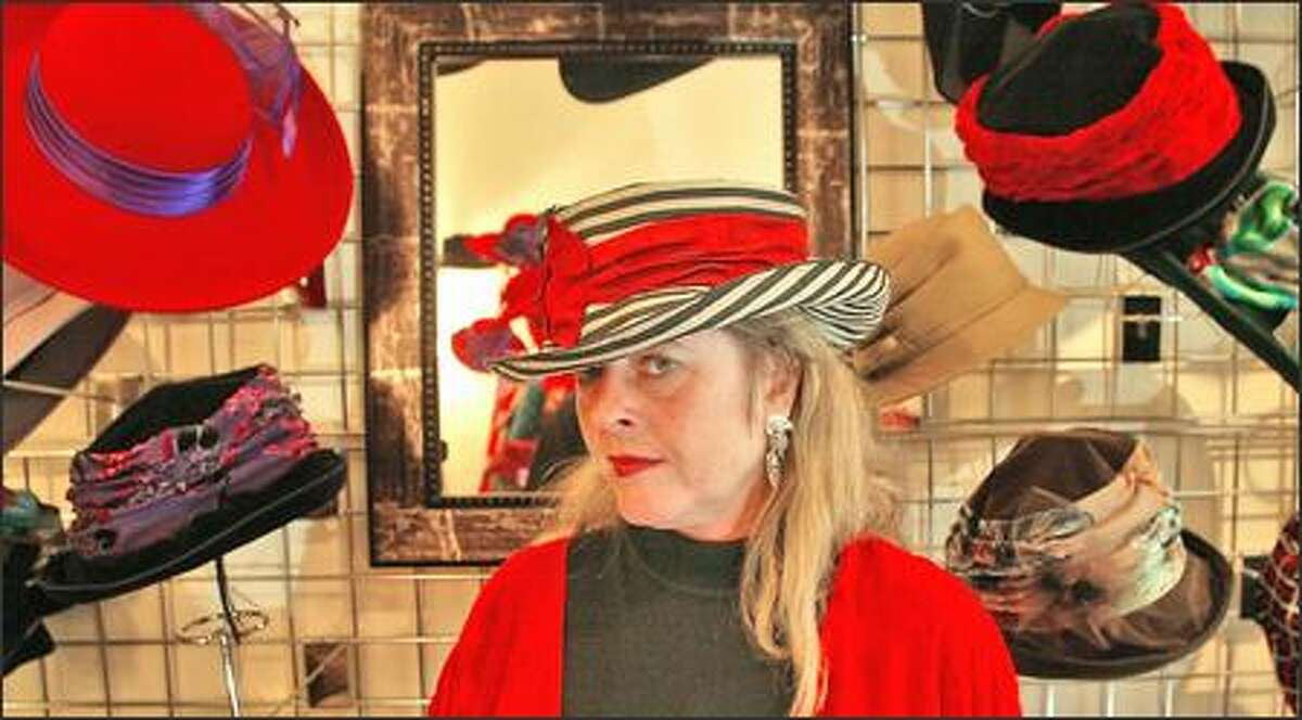 Sarah Goldenberg, the owner of Lid Wear in Ballard, in a douppioni striped Mad Hatter hat that sells for $145.