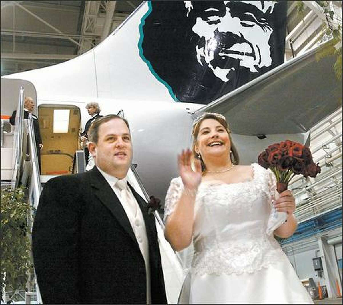 Alaska Airlines celebrated the delivery of its newest airplane, a Boeing 737-800, yesterday with an onboard wedding with employees Frank Raymond and Jennifer Genna. The plane departed from Boeing Field and touched down at Sea-Tac Airport. Raymond and Genna, shown here before boarding the airplane, planned to tie the knot over Mt. Rainier. Captain Mike Swanigan was the ceremony officiant, according to the couple's wedding invitation. The card shows an Alaska Airlines jet flying through a heart made of red balloons.