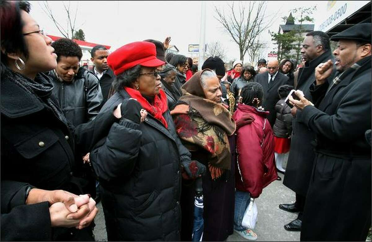 The Rev. Reggie Witherspoon, far right, and the Rev. Carey Anderson, next to Witherspoon, lead a prayer vigil Sunday at the Philadelphia Cheese Steak restaurant.