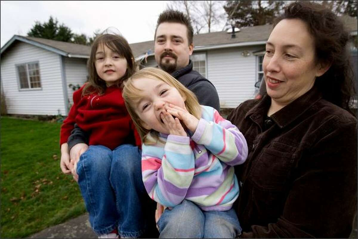 Dutch and Brecky Bihary, with daughters Arreah, 5, and Zayda, 3, stand in from of the Mount Vernon home they've had for 12 years. They recently refinanced and said they asked for a 30-year fixed-rate loan, but instead got an ARM that doubled their payments.