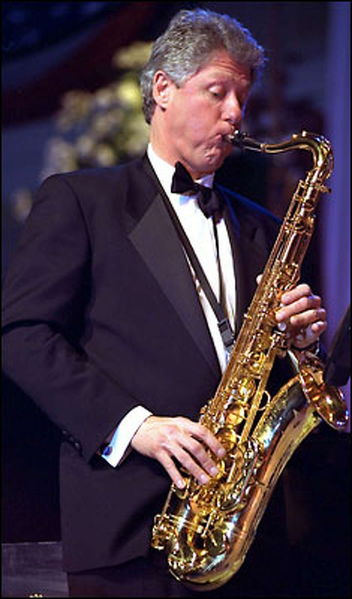 President Clinton wails on his saxophone at his 1993 inaugural ball. No, he won't take the show to Italy.