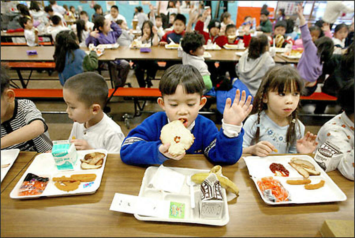Kindergartner Dickson Chen attacks a slice of pizza at Van Asselt Elementary School on Beacon Hill. Nearly 80 percent of the school's pupils qualify for free or reduced-priced lunches. The Bush administration, suspecting cheating in the federal program, proposes to require more proof of need from families.