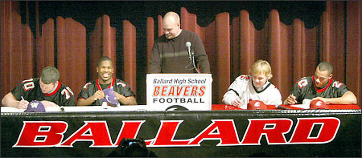 Ballard High School football coach Doug Trainor, center, savors the moment as four of his players sign national letters of intent to play for Division I rivals Washington and Washington State. From left, lineman Tyler Ashby and safety Keauntea Bankhead signed with the UW, while quarterback Cole Morgan and running back J.T. Diederichs signed with WSU.