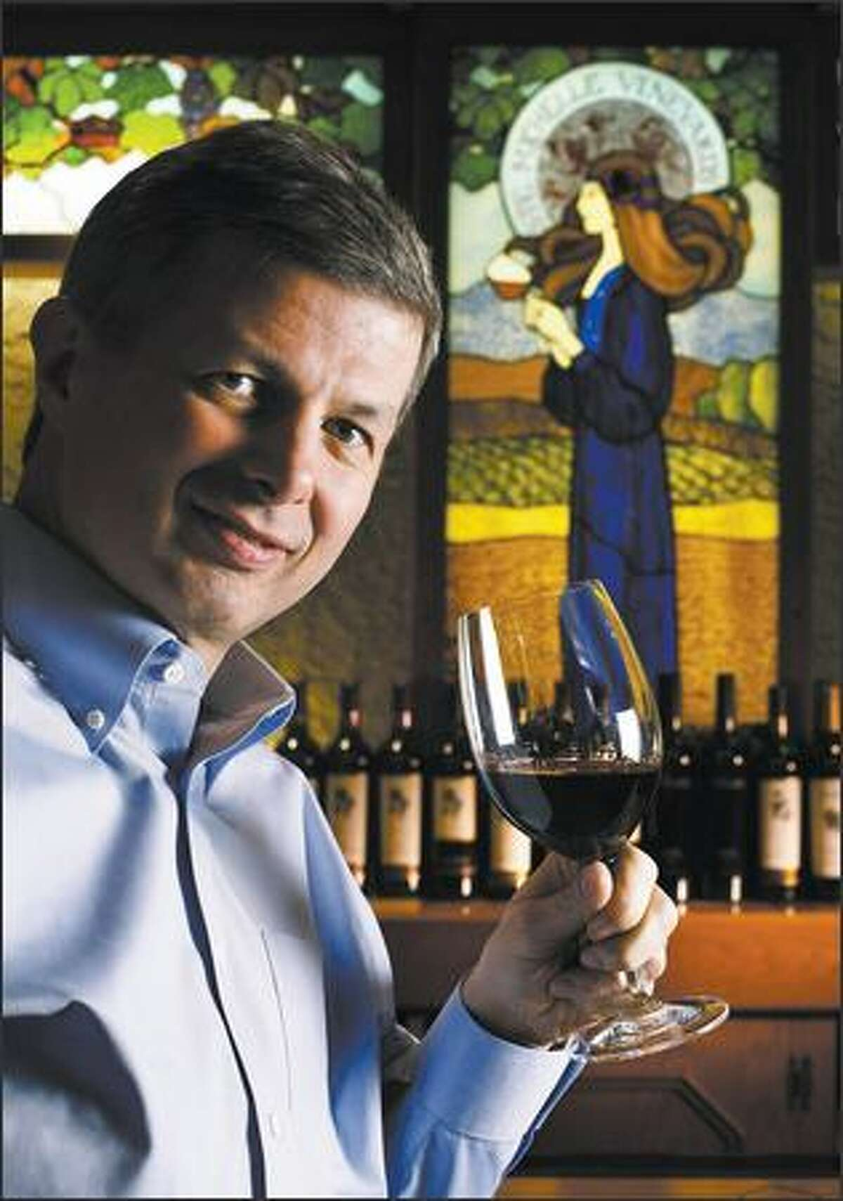 Ste. Michelle Wine Estates CEO Ted Baseler lifts a glass of 2004 Col Solare at a chateau tasting bar.