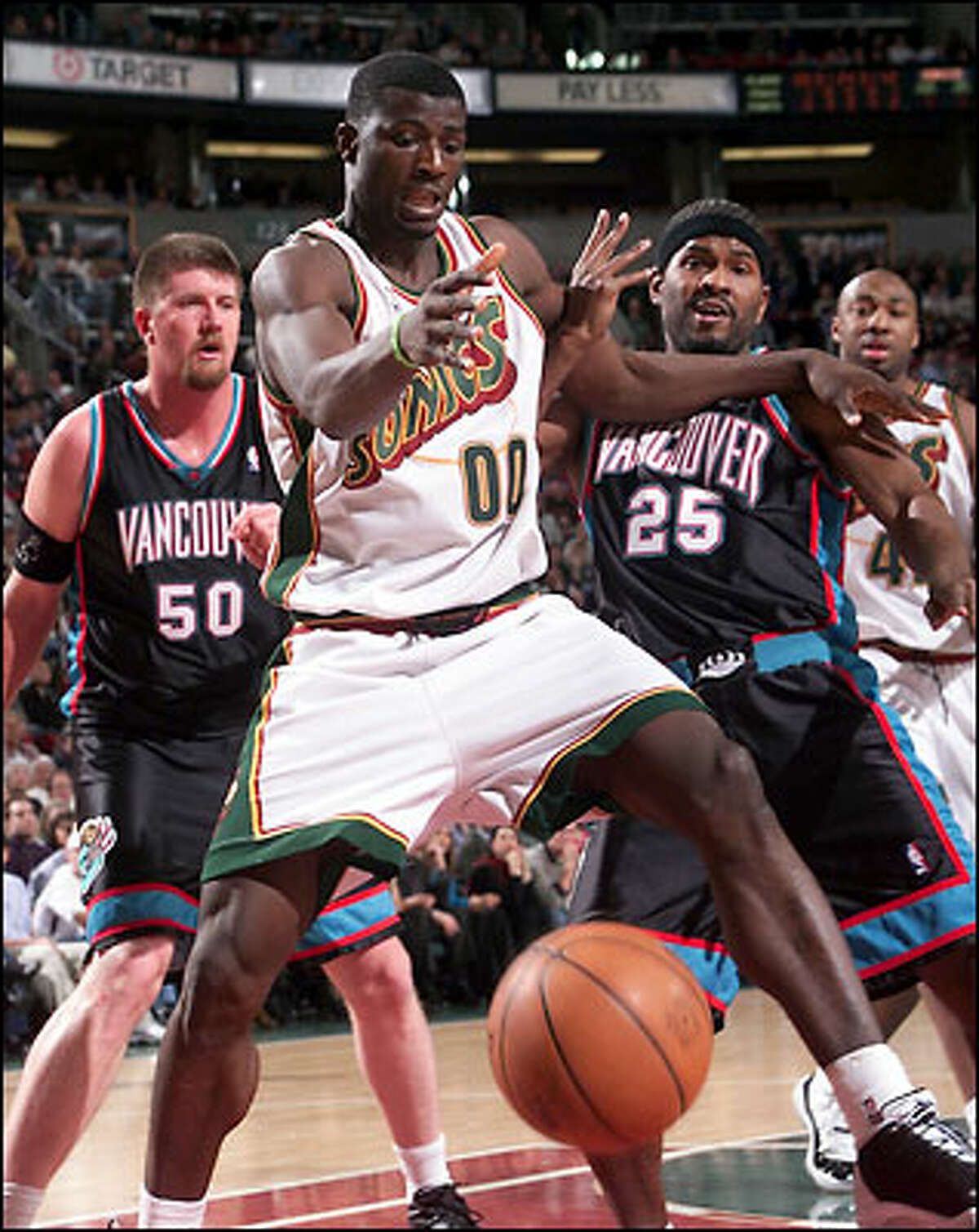Sonics player Olumide Oyedeji battles for a loose ball between Grizzlies's Bryant Reeves (50) and Erick Strickland (25) in second quarter play at KeyArena Monday.