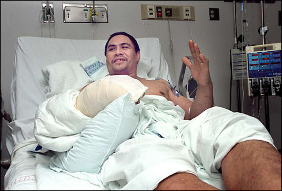 Patrick Laulu, recovering at Harborview Medical Center, talks about how he was lifted from the deck of a fishing ship off the Aleutians after his hand was severed by a fish saw. Photo: Grant M. Haller, Seattle Post-Intelligencer / Seattle Post-Intelligencer