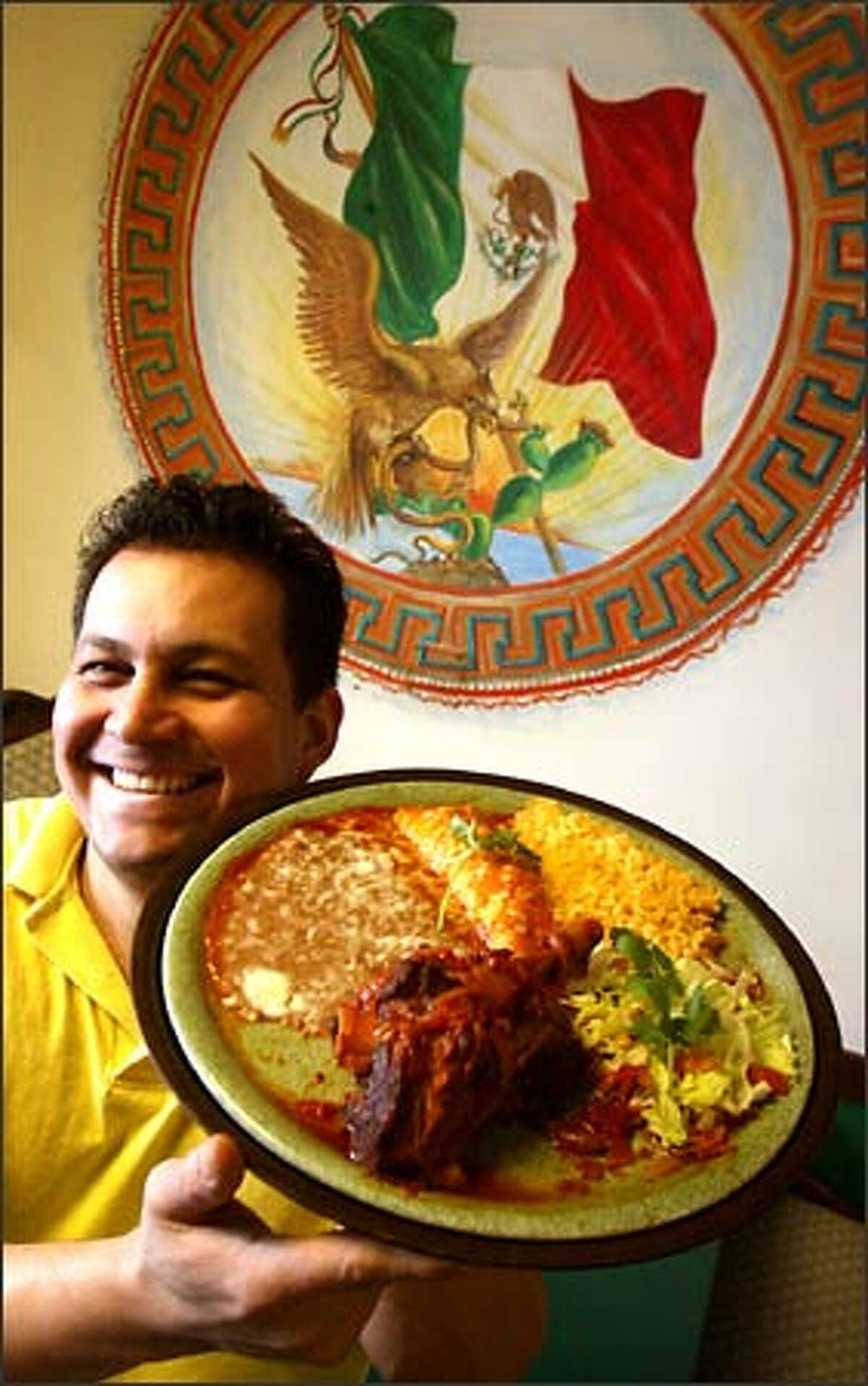 Antonio Hernandez, owner of Casa Durango, hefts a plate of lamb shank, chicken enchilada, rice and beans.
