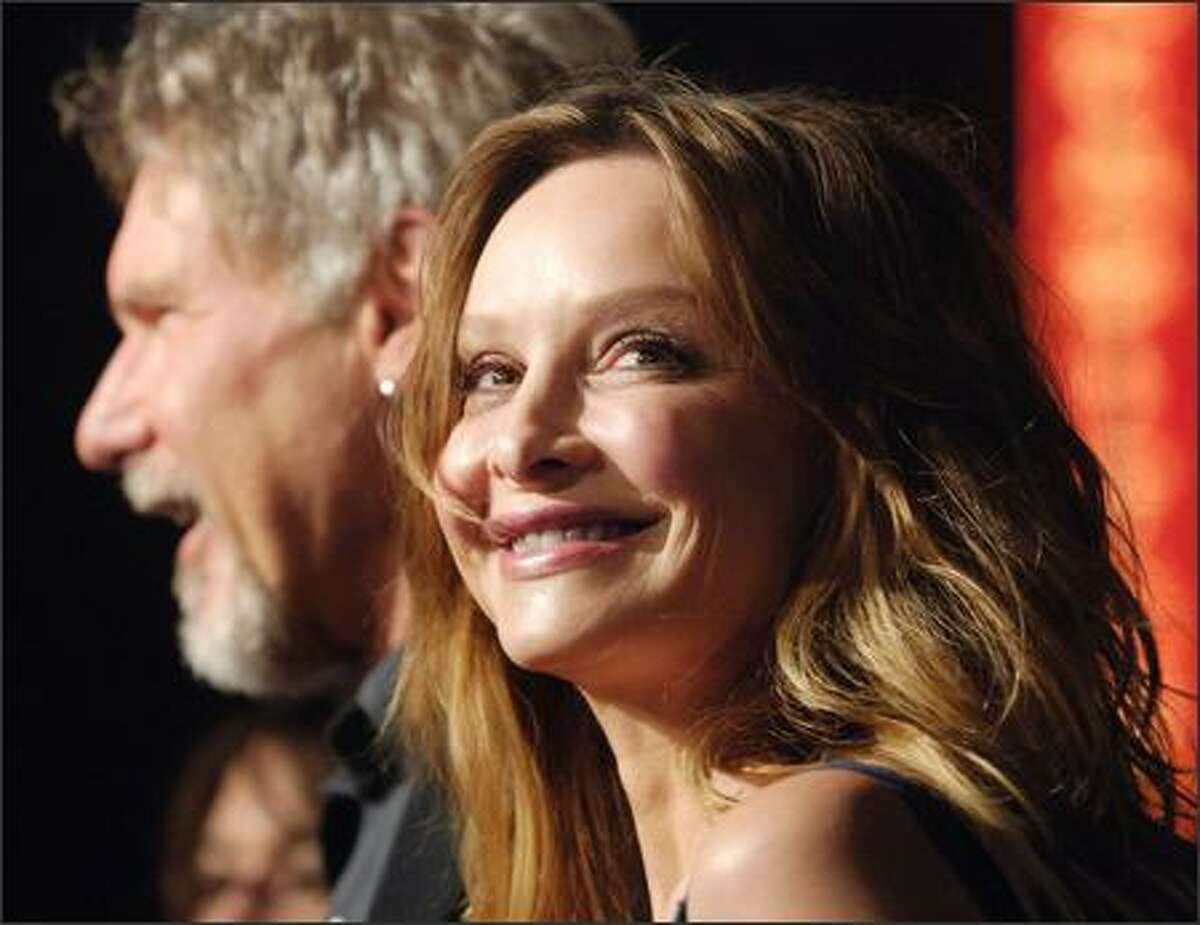 Still together, in the limelight and in the private light and probably under the cover of darkness, too, are Calista Flockhart and Harrison Ford (he be the out-of-focus one in the background with the goatee). The semireclusive couple were snapped at the L.A. premiere of Ford's latest flick,